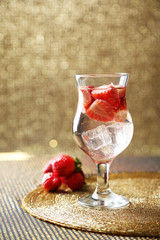 Glass of freshness water with strawberries, on bright