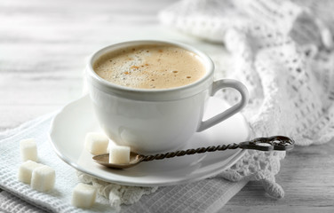 Cup of latte on wooden table, on light background