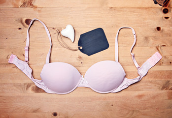 pink bra on wood background - love