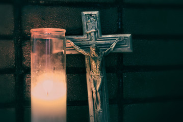 Crucifix and lighted wax candle