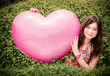A cute Thai girl is hugging giant pink heart in vintage color