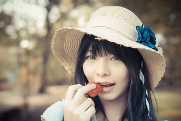 A cute Asian Thai girl with vintage clothings is biting strawber