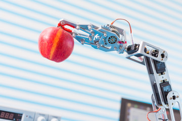 red apple in a  robot  arm
