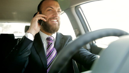 Happy smiling handsome business man driving on the phone