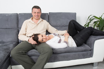 Cheerful couple on their couch smiling at camera