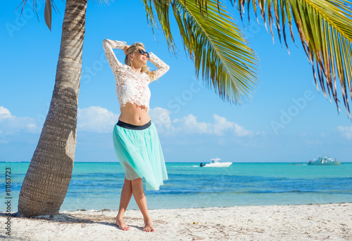 Happy carefree woman on tropical beach under palm tree