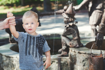 Little boy standing next to fountain in wet t-shirt