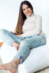Beautiful young woman looking at camera at home.