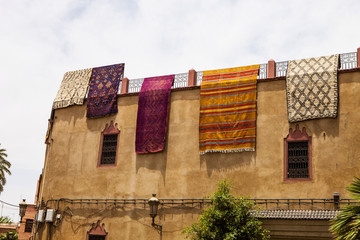 colorful carpets dried on the walls of houses, Morocco