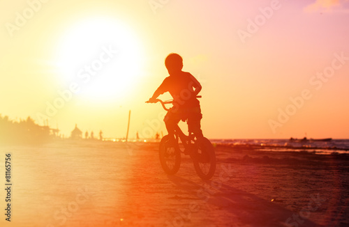 little boy riding bike at sunset - 81165756
