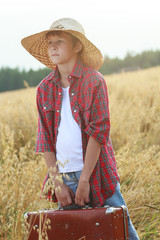 Teenage traveler in oat field holding old-fashioned suitcase