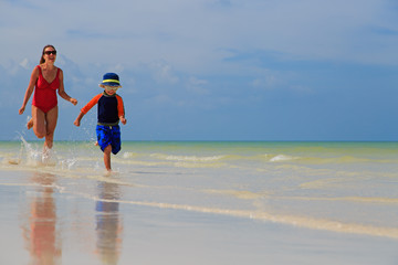 mother and son running in water on the beach