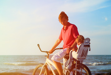 father and baby biking at summer beach