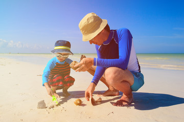 father and son building sand castle on summer beach