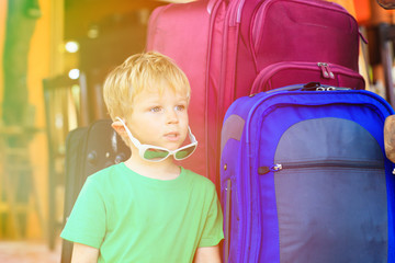 little boy sitting on suitcases ready to travel