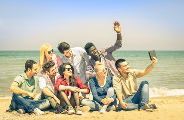 Multiracial happy friends taking selfie with tablet at beach