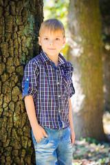 Stylish cute boy posing near a tree