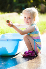 toddler girl playing with water sprayer in summer