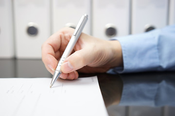 closeup of businessman hand with pen when signing document. Busi