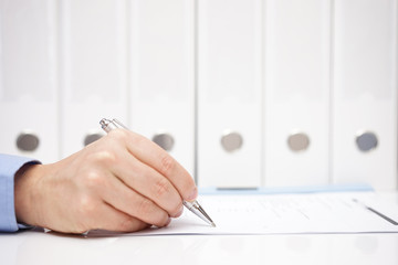 Businessman or accountant is signing document with binders in ba