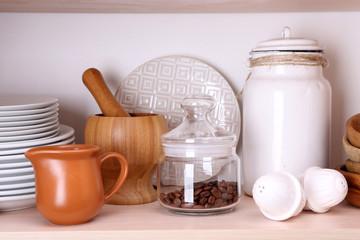 Kitchen utensils and tableware on wooden shelf