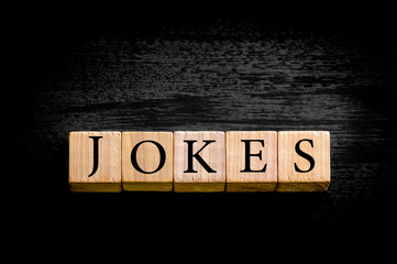 Word JOKES isolated on black background with copy space