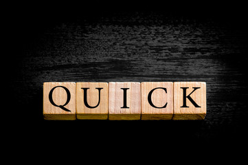 Word QUICK isolated on black background with copy space