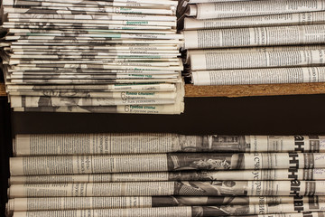 A stack of old newspapers lie on the shelf