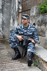 Caucasian military man in urban warfare sitting and holding auto