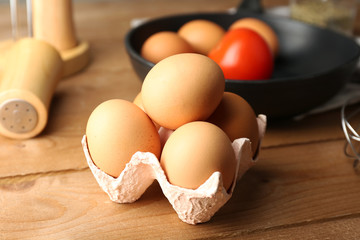 Still life with eggs and pan on wooden table, closeup