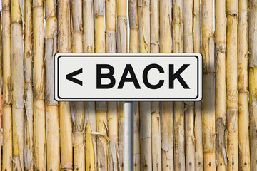"The word ""Back"" written on a road sign against a fence wattle"