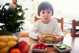 Beautiful little boy, eating sandwich at home, vegetables on the - 81173993