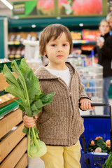 Cute little and proud boy helping with grocery shopping, healthy