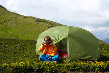Young lady sitting near a tent in front of snowy mountain peaks