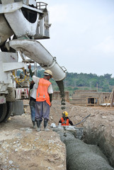 Group of construction workers pouring concrete
