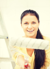 happy young woman with paintroller