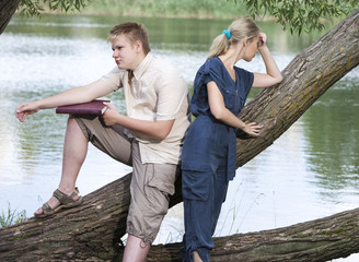 guy and the girl in quarrel on the bank of the lake