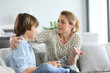 Leinwanddruck Bild - Mother giving warning to young boy using smartphone