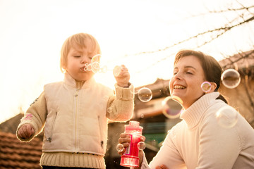 Happy childhood - mother and child blowing soap bubbles