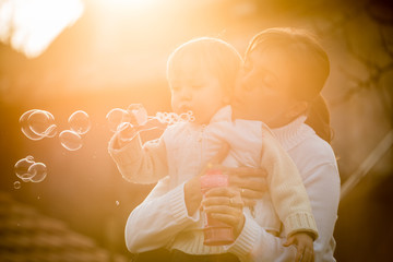 Mother and child blowing together soap bubbles