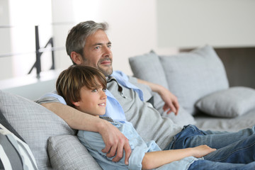 Father and son relaxing in sofa a thome