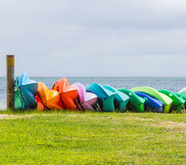 Many colorful kayaks orderly dock on the beach