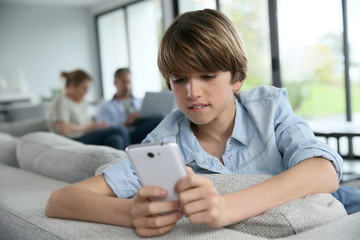Teenage boy using smartphone at home