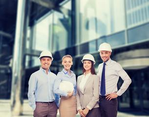 group of smiling businessmen in white helmets