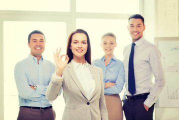 smiling businesswoman showing ok-sign in office