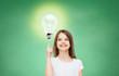 smiling school girl pointing finger to light bulb