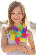 happy girl with colorful pinwheel toy