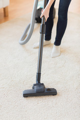 close up of woman legs with vacuum cleaner at home