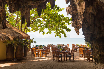 view to open-air restaurant on beach from cave