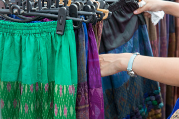 close up of hands choosing skirts at street market